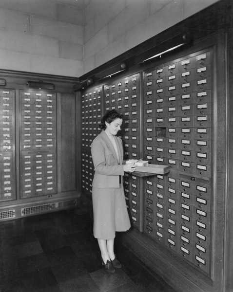 Woman using card catalog